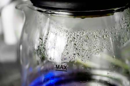 Turbid water inside misted glass teapot with shiny drops in bright sunlight. Closeup of boiled water in old transparent kettle on kitchen. Close-up, selective focus.