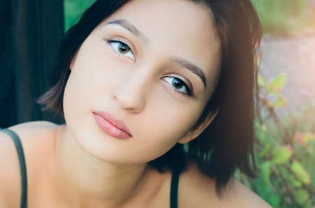 Portrait of a beautiful girl with short dark hair looking at the camera.
