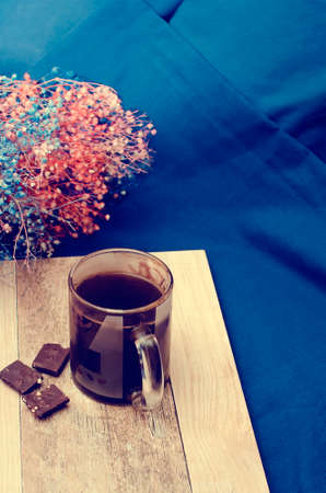 Hot coffee with chocolate on the background of the bed. Blue linens. Lifestyle concept. Vertical photography.