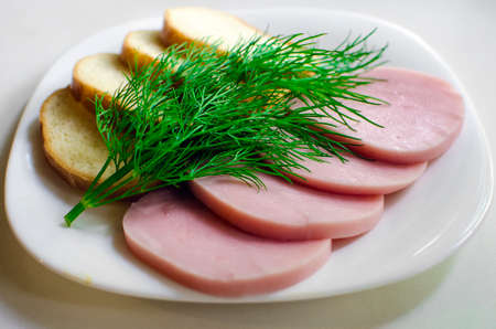 Pieces of sausage, bread and dill on a plate. Homemade food. Standard-Bild