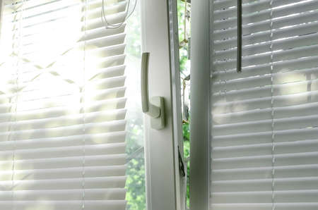 A plastic window with blinds is open for ventilation mode.