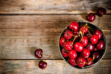 dark cherry: cherries on a dark wood background. toning. selective focus on cherry in the bowl