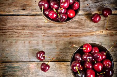 dark cherry: cherries on a dark wood background. toning. selective focus on cherry in the lower bowl
