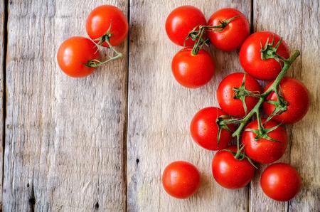 tomate: tomates cerises rouges sur un fond de bois blanc. tonifiant. mise au point s�lective sur les bonnes tomates