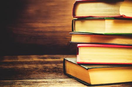 libros: Pila de libros en el fondo de madera oscura. tonificaci�n. atenci�n selectiva en el libro medio