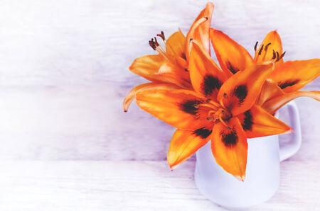 lilia: flores anaranjadas lilia sobre un fondo de madera blanca. tonificaci�n. enfoque selectivo en el medio de la flor Foto de archivo