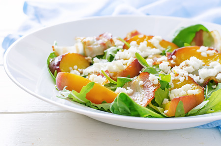 goat peach: salad with peaches, bacon; arugula, spinach and goat cheese on a light background. toning. selective focus on bacon.