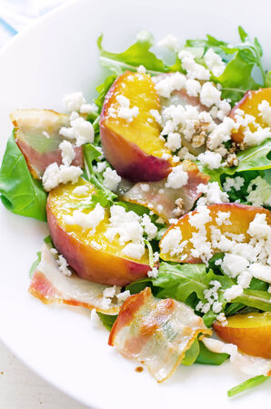 goat peach: salad with peaches, bacon; arugula, spinach and goat cheese on a light background. toning. selective focus on left peach. Stock Photo