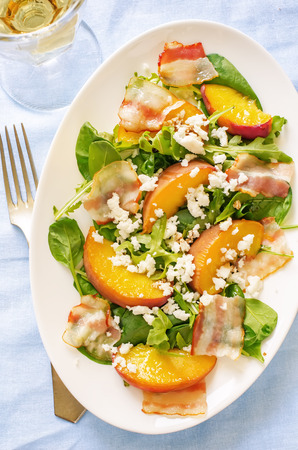 salad with peaches, bacon; arugula, spinach and goat cheese on a light background. toning. selective focus on the middle salad.