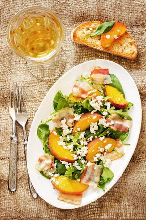 goat peach: salad with peaches, bacon; arugula, spinach and goat cheese on a dark background. toning. selective focus on middle salad.