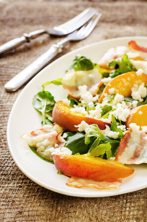 salad with peaches, bacon; arugula, spinach and goat cheese on a dark background. toning. selective focus on the front peach.