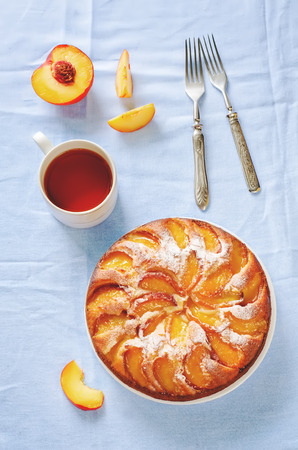 custard flavor: cake with peaches on a blue background. toning. selective focus on the middle of the pie Stock Photo