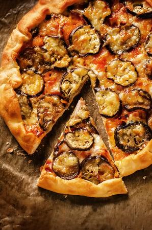 暗い背景にナスのピッツァ。着色。ピザのスライスの選択と集中