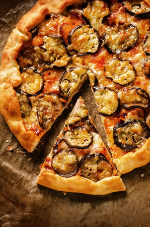 pizza with eggplant on a dark background. tinting. selective focus on a slice of pizza 版權商用圖片