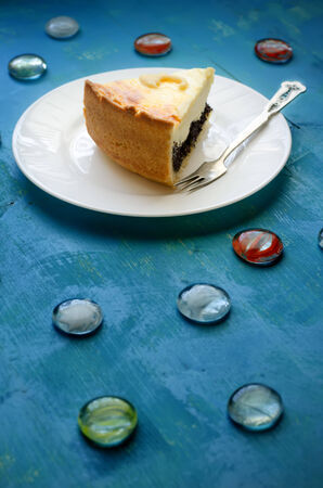 cottage cheese and poppy seed cake with embellishments in the shape of umbrellas on a blue background. Focus on the piece of the pie. photo