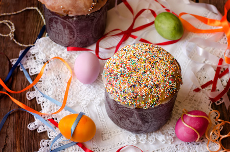 confect: Easter cake and eggs on the white cloth with colorful ribbons Stock Photo