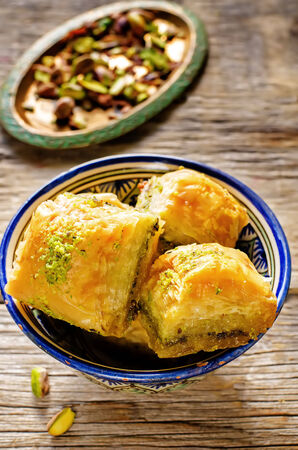 baklava with pistachio. turkish traditional delight on a dark wood background. toning. selective focus on left baklava photo