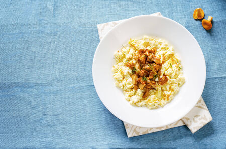 tinting: scrambled eggs with fried chanterelles on a blue background. tinting. selective focus on chanterelles