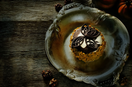 pumpkin cheesecake with chocolate and walnuts on a dark wood background. tinting. selective focus photo