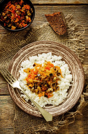 tinting: rice with sauce of eggplant, peppers and tomatoes on a dark wood background. tinting. selective focus on the eggplant in the dish Stock Photo