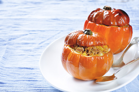 tinting: baked pumpkin stuffed with beef and vegetables on a blue background. tinting. selective focus on the filling