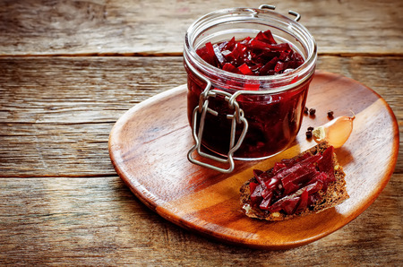 tinting: pickled beets in the jar on a dark wood background. tinting. selective focus on the beet on the bread Stock Photo