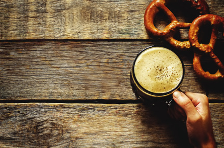man holding beer on a dark wood background. tinting. selective focus on the arm photo