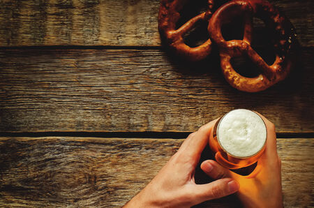 beer background: man holding beer on a dark wood background. tinting. selective focus on the foam in the glass Stock Photo