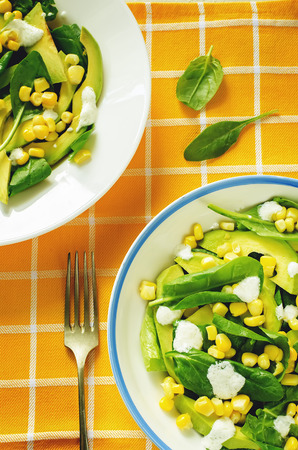 tinting: salad with corn, spinach and avocado on a yellow background. tinting. selective focus on the middle of the bottom salad