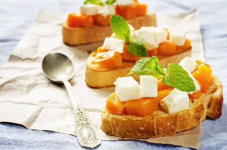 tinting: bruschetta with honey pumpkin and goat cheese on a blue background. tinting. selective focus on mint Stock Photo