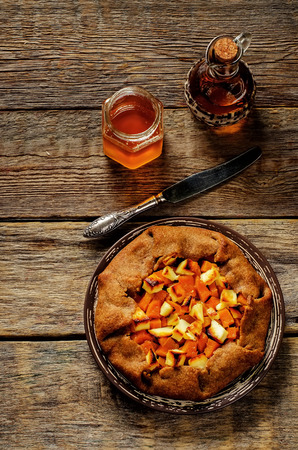 tinting: rye galette with honey pumpkin and goat cheese on a dark wood background. tinting. selective focus on the middle of galette