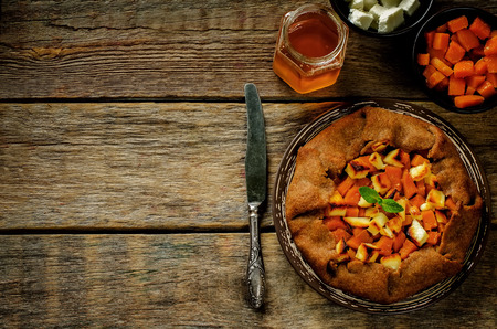 tinting: rye galette with honey pumpkin and goat cheese on a dark wood background. tinting. selective focus on mint Stock Photo