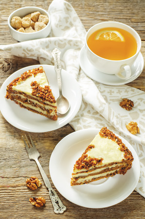 tinting: carrot cake with raisins, walnuts and butter cream on a dark wood background. tinting. selective focus on the bottom cake