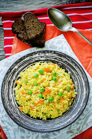 pongal: Indian vegetarian pilaf, Biriyani, with carrots and green peas on a dark wood background. tinting. selective focus on the middle pilaf Stock Photo