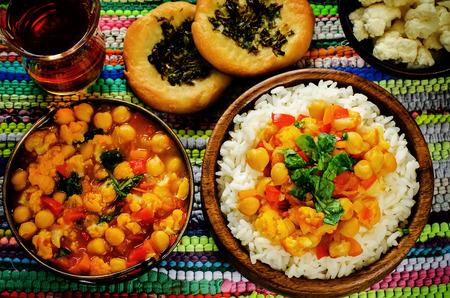 야채와 여러 가지 빛깔 배경에 허브와 함께 아랍어 평평한 빵과 카레 병아리 콩과 쌀. 색조. 쌀의 중간에 선택적 포커스