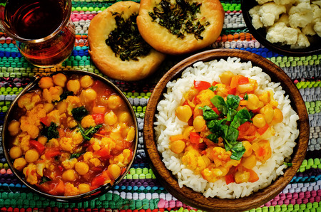 rice with curry chickpeas with vegetables and Arabic flat bread with herbs on a multicolored background. tinting. selective focus on the middle of the rice
