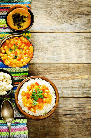 pongal: rice with curry chickpeas with vegetables and Arabic flat bread with herbs on a dark wood  background. tinting. selective focus on the middle of the rice