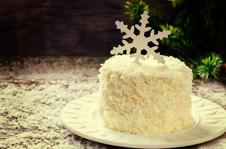 coconut chocolate cake with cream cheese on a dark wood background. tinting. selective focus on a snowflake photo