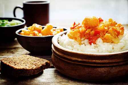 rice with curry cauliflower on a dark wood background. tinting. selective focus on the middle of the rice