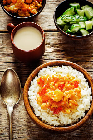 pongal: rice with curry cauliflower on a dark wood  Stock Photo