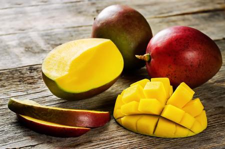 mango fruta: mango sobre un fondo de madera oscura. tintado. selectivo se centran en los mangos rebanadas