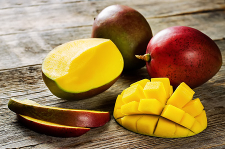 mango on a dark wood background. tinting. selective focus on the mangos slices