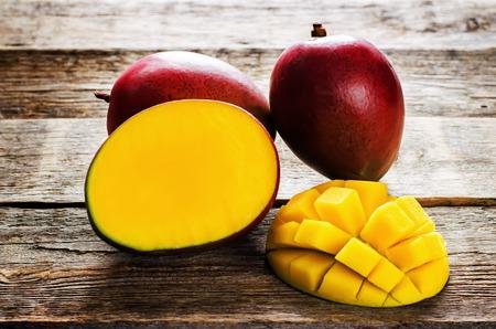 mango fruta: mango en un fondo de madera oscura. tintado. atenci�n selectiva en los mangos rebanadas