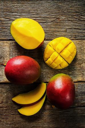 mango on a dark wood background. tinting. selective focus on the mangos slices Imagens - 33245257