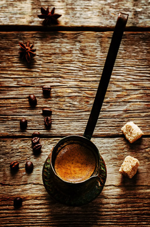 cezve: black coffee in the cezve on a dark wood background. tinting. selective focus on coffee