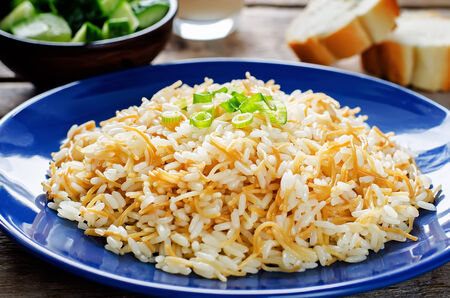 pongal: Rice with vermicelli on a dark wood background. Traditional Arabic dish. tinting. selective focus on green onions Stock Photo