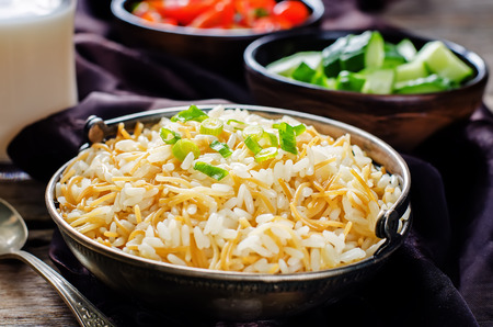pongal: Rice with vermicelli on a dark background. Traditional Arabic dish. tinting. selective focus on green onions Stock Photo