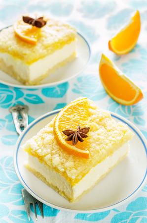 cake met sinaasappel, roomkaas en kruimels op een lichte achtergrond. verven. selectieve aandacht voor de steranijs