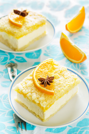 cake with orange, cream cheese and crumbs on a light background. tinting. selective focus on the star anise Stock Photo