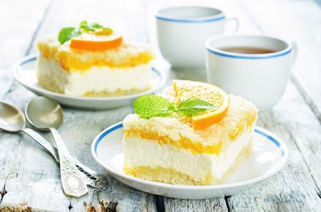 오렌지, 크림 치즈와 빛 나무 배경에 부스러기와 케이크. 착색. 민트에 선택적 초점